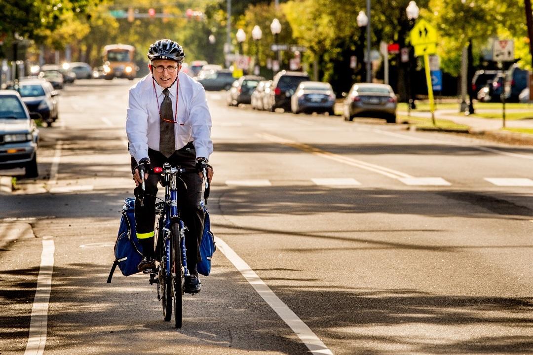 Employee biking to work in business attire