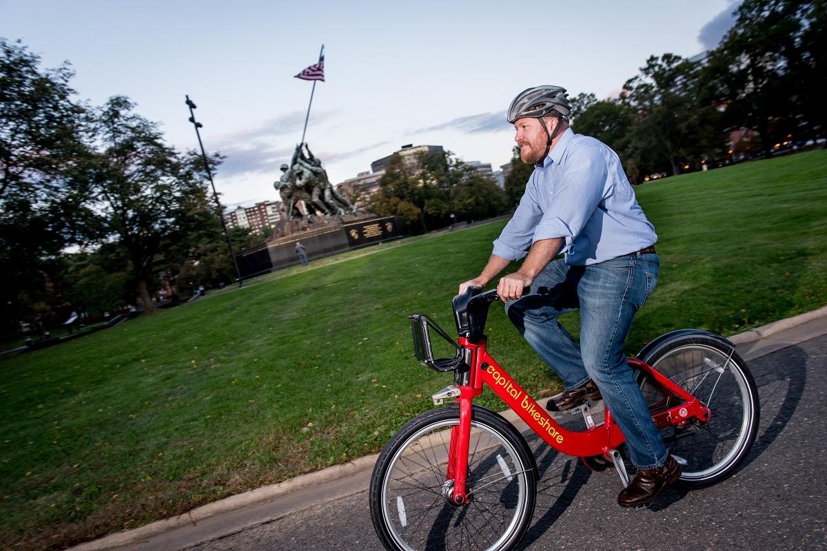 man riding capital bikeshare in front of iwo jima memorial