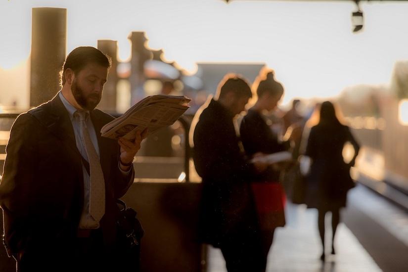 man-reading-paper-metro-platform