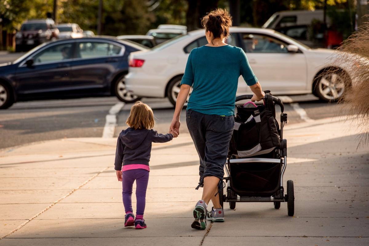 woman-holding-kids-hand-stroller