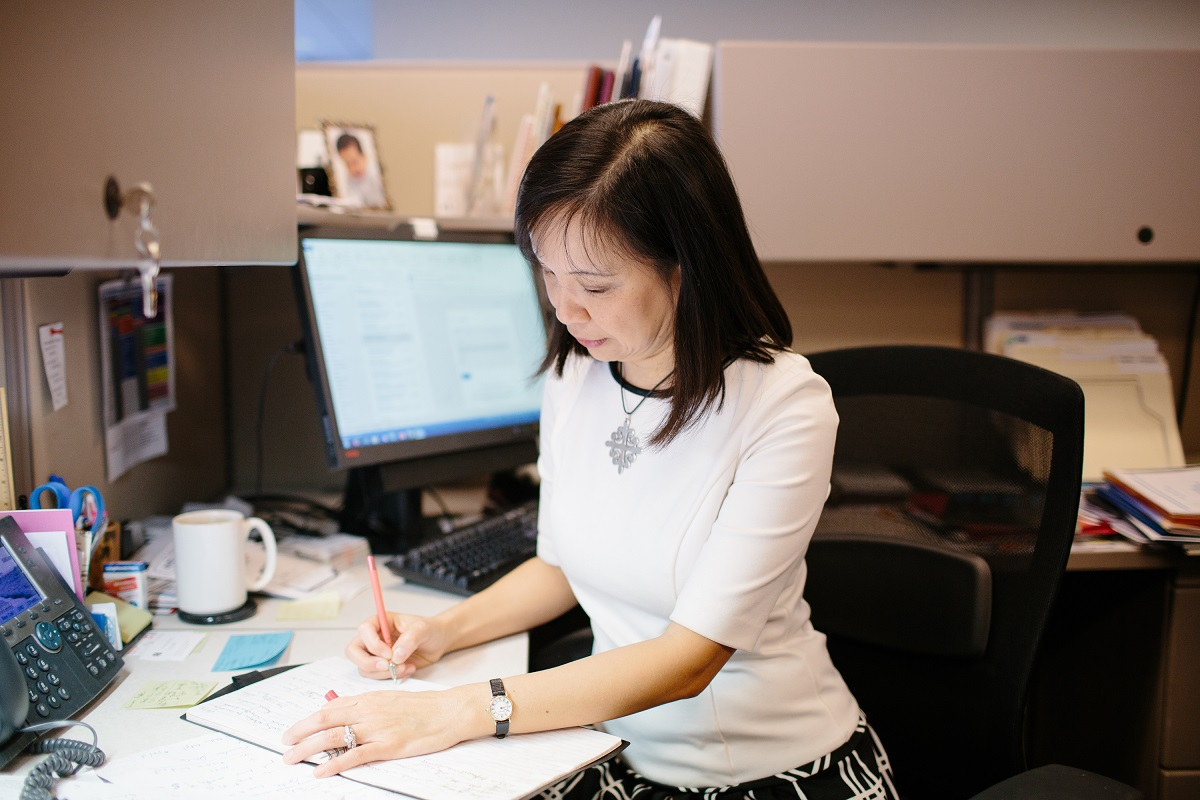 woman-working-at-desk-writing