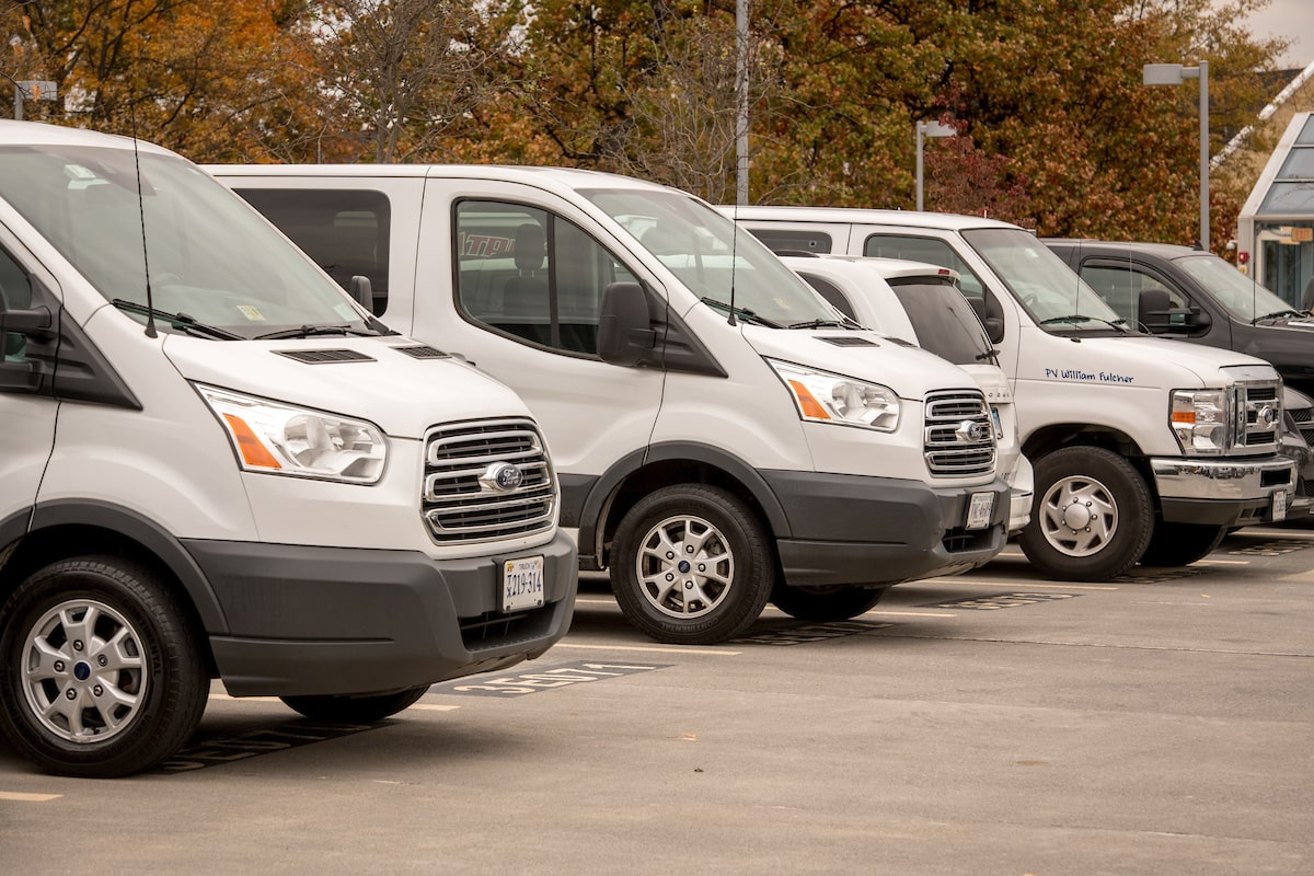 group of white vans in parking lot-1