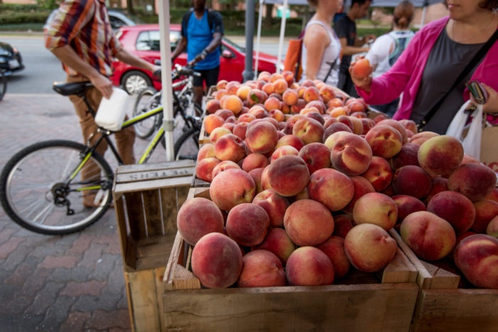 Farmers market peaches and biker walking by